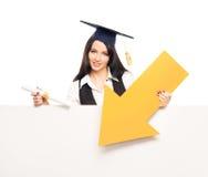 Ένας απόφοιτος φοιτητής με ένα κίτρινο βέλος Στοκ φωτογραφία με δικαίωμα ελεύθερης χρήσης