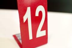 Ένας αριθμός δώδεκα που τυπώνεται στο λευκό με το κόκκινο υπόβαθρο Στοκ εικόνες με δικαίωμα ελεύθερης χρήσης