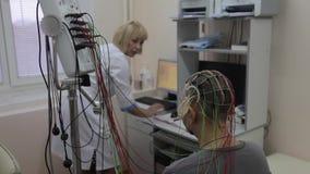 Ένας αρσενικός ασθενής κάθεται σε μια καρέκλα Στο κεφάλι και τα χέρια του είναι συνδεδεμένοι ιατρικές συσκευές και αισθητήρες για απόθεμα βίντεο