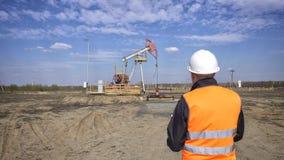 Ένας αρσενικός επιθεωρητής-χειριστής σε μια φανέλλα σημάτων και ένα άσπρο κράνος καταγράφει τις αναγνώσεις για το πετρέλαιο αντλώ στοκ εικόνα