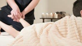 Ένας αρσενικός μασέρ φυσιοθεραπευτών κάνει ένα θεραπεύοντας χαλαρώνοντας μασάζ και τέντωμα ενός μικρού αγοριού σε ένα κρεβάτι μασ απόθεμα βίντεο