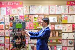 Ένας αρσενικός πελάτης που κοιτάζει βιαστικά τις κάρτες ημέρας Mother's σε χαρτικά ST στοκ φωτογραφία με δικαίωμα ελεύθερης χρήσης