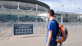 Ένας αρσενικός τουρίστας εξετάζει ένα σημάδι με τα απαγορευμένα στοιχεία πρίν παρευρίσκεται σε έναν αγώνα ποδοσφαίρου στην πόλη τ στοκ εικόνα με δικαίωμα ελεύθερης χρήσης