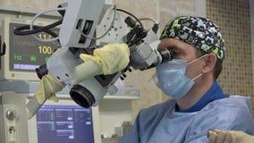 Ένας αρσενικός χειρούργος εκτελεί μια μικροσκοπική λειτουργία στα ΩΤΟΡΙΝΟΛΑΡΥΓΓΟΛΟΓΙΚΑ όργανα ενός ασθενή χρησιμοποιώντας ένα χει φιλμ μικρού μήκους