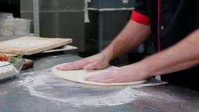 Ένας αρχιμάγειρας στην κουζίνα εστιατορίων που διαμορφώνει μια ζύμη για την πίτσα που χρησιμοποιεί ένα αλεύρι απόθεμα βίντεο