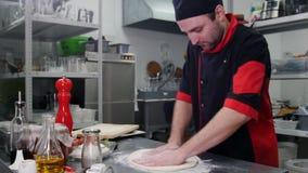 Ένας αρχιμάγειρας στο εστιατόριο που διαμορφώνει μια ζύμη για την πίτσα που χρησιμοποιεί ένα αλεύρι απόθεμα βίντεο