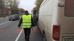 Ένας αστυνομικός ελέγχει την κυκλοφορία στην εθνική οδό κοντά σε ένα οδόφραγμα μπροστά από την πόλη του Κίεβου, Ουκρανία απόθεμα βίντεο
