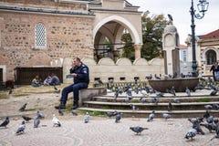 Ένας αστυνομικός κάθεται κοντά στην πηγή στην αχρηστία που συσσωρεύεται με τα περιστέρια και μιλά στο ραδιόφωνο, τρεις ξένοι νεαρ στοκ εικόνα