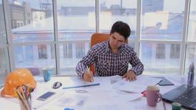 Ένας βέβαιος και ελκυστικός επιχειρηματίας που εργάζεται με τα σχέδια, σχεδιαγράμματα σε ένα ελαφρύ, σύγχρονο γραφείο χρυσή ιδιοκ απόθεμα βίντεο