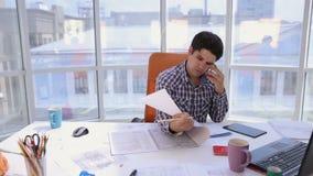Ένας βέβαιος και ελκυστικός επιχειρηματίας που εργάζεται με τα σχεδιαγράμματα, ομιλούν τηλέφωνο σε ένα ελαφρύ, σύγχρονο γραφείο Ε φιλμ μικρού μήκους