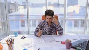 Ένας βέβαιος και ελκυστικός επιχειρηματίας που εργάζεται με τα σχεδιαγράμματα, ομιλούν τηλέφωνο σε ένα ελαφρύ, σύγχρονο γραφείο Ε απόθεμα βίντεο