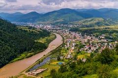 Ένας βαθύς, λασπώδης ποταμός σε μια πράσινη σειρά βουνών έχει επισημάνει το χωριό από τον εξωτερικό κόσμο Μια θέση της ηρεμίας κα Στοκ εικόνες με δικαίωμα ελεύθερης χρήσης