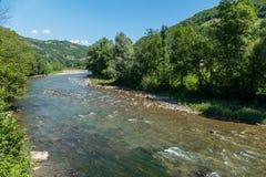 Ένας βαθύς μπλε ουρανός με τα σύννεφα και τα βουνά κατωτέρω και ο τρέχων ποταμός με ένα φύκι-καλυμμένο κατώτατο σημείο στοκ εικόνες