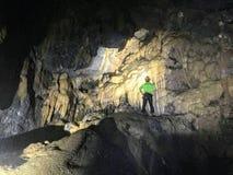 Ένας βιετναμέζικος ξεναγός λάμπει το επικεφαλής φως προβολέων του προς έναν σχηματισμό σταλαγμιτών στον ογκώδη κρεμά τη σπηλιά Va στοκ φωτογραφίες με δικαίωμα ελεύθερης χρήσης