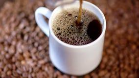 Ένας βράζοντας στον ατμό καυτός σκοτεινός καφές χύνεται σε μια άσπρη κεραμική κούπα απόθεμα βίντεο