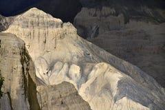 Ένας βράχος, απότομος βράχος του κιτρινωπού χρώματος με μια οξείας γωνίας αιχμή μεταξύ των σκοτεινών βουνών Στοκ Εικόνα