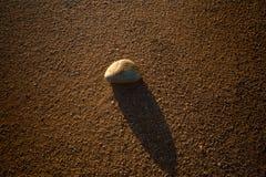 Ένας βράχος και η σκιά του πέρα από την άμμο σε μια έρημο στοκ φωτογραφία