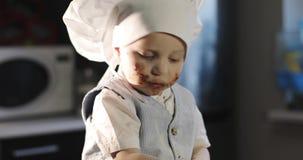 Ένας βρώμικος μικρός μάγειρας γλείφει ένα δίκρανο με τη σοκολάτα απόθεμα βίντεο