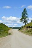 Ένας βρώμικος δρόμος με έναν μπλε ουρανό και τα σύννεφα Στοκ Φωτογραφία