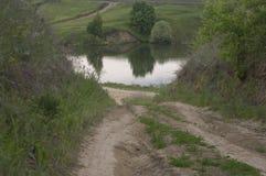 Ένας βρώμικος δρόμος που οδηγεί σε μια λίμνη Στοκ Εικόνες