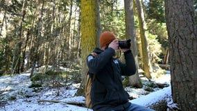 Ένας γενειοφόρος αρσενικός ταξιδιωτικός φωτογράφος με τη κάμερα του στο χειμερινό δάσος παίρνει τις εικόνες της φύσης Έννοια ταξι φιλμ μικρού μήκους