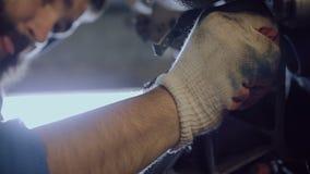 Ένας γενειοφόρος μηχανικός αυτοκινήτων στρίβει το μπουλόνι στην κατοικία μηχανών φιλμ μικρού μήκους