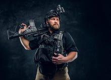 Ένας γενναίος στρατιώτης ειδικών δυνάμεων που φορά τις στολές αγώνα με τις σύγχρονες συσκευές που θέτουν με ένα επιθετικό τουφέκι στοκ φωτογραφίες