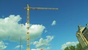 Ένας γερανός πύργων κατασκευής, ενάντια σε έναν μπλε ουρανό με την κίνηση των άσπρων σύννεφων Χρονικές περιτυλίξεις απόθεμα βίντεο