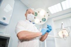 Ένας γιατρός αναισθησιολόγων κρατά μια σύριγγα στα χέρια του και εξετάζει το πλαίσιο Στοκ Φωτογραφία