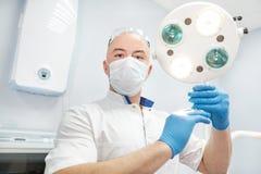 Ένας γιατρός αναισθησιολόγων κρατά μια σύριγγα στα χέρια του και εξετάζει το πλαίσιο Στοκ εικόνα με δικαίωμα ελεύθερης χρήσης