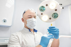 Ένας γιατρός αναισθησιολόγων κρατά μια σύριγγα στα χέρια του και εξετάζει το πλαίσιο Στοκ Εικόνες