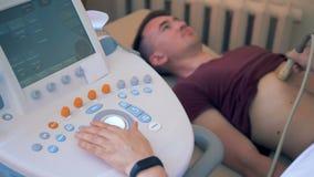 Ένας γιατρός ανιχνεύει το υπομονετικό στομάχι ` s Ένας γιατρός εκτελεί το ultrasonography σε έναν αρσενικό ασθενή σε μια κλινική απόθεμα βίντεο