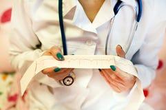 Ένας γιατρός με ένα στηθοσκόπιο ελέγχει ένα καρδιογράφημα ασθενών Στοκ Φωτογραφία