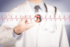 Ένας γιατρός που κρατά ένα χάπι καρδιών Στοκ εικόνα με δικαίωμα ελεύθερης χρήσης