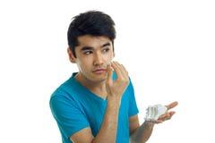 Ένας γοητευτικός νεαρός άνδρας σε μια μπλε μπλούζα κοιτάζει μακριά και προκαλεί τον αφρό στο πρόσωπό σας Στοκ Εικόνα