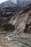 Ένας γρήγορος ποταμός βουνών ρέει κατά μήκος των πετρωδών κλίσεων των γκρίζων βουνών Καύκασου Στοκ εικόνα με δικαίωμα ελεύθερης χρήσης