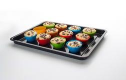 Ένας δίσκος ψησίματος που γεμίζουν με muffins με τις φόρμες σιλικόνης του στοκ φωτογραφίες