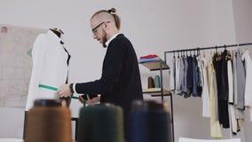 Ένας δημιουργικός ράφτης ή ένας σχεδιαστής μόδας κάνει τις μετρήσεις ενός άσπρου σακακιού σε ένα ομοίωμα στο στούντιό του για το  απόθεμα βίντεο