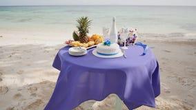 Ένας διακοσμημένος γαμήλιος πίνακας με τα φρούτα, τα γυαλιά κέικ, σαμπάνιας και κρασιού σε μια αμμώδη ωκεάνια παραλία Τροπικός έν απόθεμα βίντεο