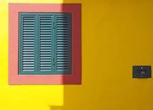 ένας δονούμενος κίτρινος τοίχος με το κόκκινο πλαίσιο και τα πράσινα κλειστά κλείνω με παντζούρια χαρακτηριστικά πορτογαλικά χρώμ στοκ φωτογραφίες