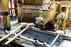 Ένας δράκος πετρών κοιτάζει πέρα από μια γούρνα νερού για τον καθαρισμό χεριών στοκ φωτογραφία