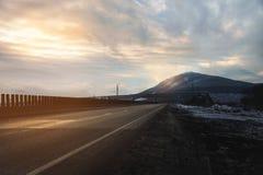 Ένας δρόμος ασφάλτου χωρών που φωτίζεται από τις ακτίνες του ήλιου μέσω των σύννεφων που οδηγούν στο βουνό στο οποίο οι ακτίνες Στοκ φωτογραφίες με δικαίωμα ελεύθερης χρήσης