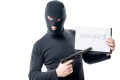 Ένας εγκληματίας με ένα πυροβόλο όπλο απαιτεί λύτρα 1000000 $ Στοκ φωτογραφία με δικαίωμα ελεύθερης χρήσης
