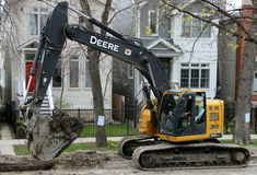 Ένας εκσκαφέας αντιολισθητικών αλυσίδων σκάβει το ρύπο σε ένα Σικάγο κατοικημένο Στοκ Φωτογραφία
