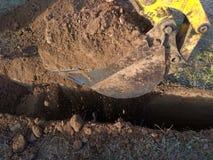 Ένας εκσκαφέας εργασίας που σκάβει μια τάφρο για το ίδρυμα ενός κτηρίου στοκ εικόνες