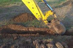 Ένας εκσκαφέας εργασίας σκάβει μια τάφρο σε ένα εξοχικό σπίτι στοκ φωτογραφίες με δικαίωμα ελεύθερης χρήσης