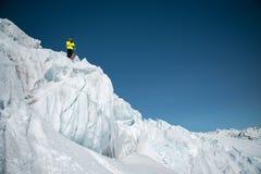 Ένας ελεύθερος σκιέρ στην πλήρη εξάρτηση στέκεται σε έναν παγετώνα στο βόρειο Καύκασο Σκιέρ που προετοιμάζεται πρίν πηδά από στοκ εικόνα