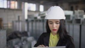 Ένας ελκυστικός υπάλληλος αποθηκών εμπορευμάτων θηλυκών που φορά τον υψηλό ιματισμό διαφάνειας και ένα σκληρό καπέλο εργάζεται σε απόθεμα βίντεο