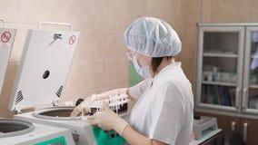 Ένας ενήλικος θηλυκός γιατρός σε ένα άσπρο υγιεινά γάντια εργαστηρίων παλτό και τοποθετεί τις εξετάσεις αίματος που αποθηκεύονται φιλμ μικρού μήκους