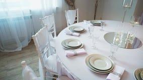 Ένας εξυπηρετούμενος πίνακας με ένα άσπρο ύφασμα στο οποίο υπάρχουν πιάτα και πετσέτες απόθεμα βίντεο